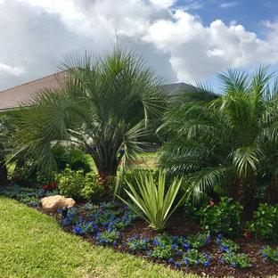 Design ideas for a mid-sized tropical partial sun backyard mulch formal garden in Orlando.