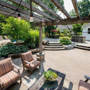 Großer, Halbschattiger Klassischer Garten im Sommer, hinter dem Haus mit Kamin und Natursteinplatten in Sonstige