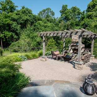 Design ideas for a large traditional partial sun backyard stone landscaping in Other with a fireplace for summer.