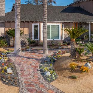 Exotisk inredning av en mellanstor trädgård i full sol som tål torka och framför huset, med en trädgårdsgång och grus