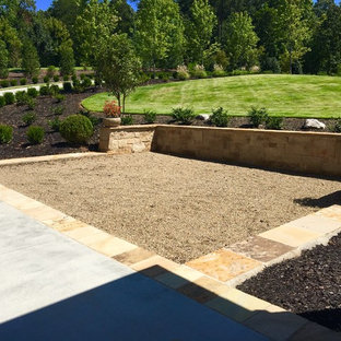 This is an example of a large traditional partial sun front yard concrete paver driveway in Other.