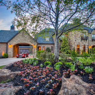 Photo of a huge rustic partial sun front yard concrete paver driveway in Oklahoma City.