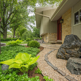 Design ideas for a mid-sized asian partial sun front yard stone landscaping in Milwaukee.