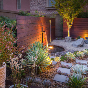 Inspiration for a mid-sized contemporary partial sun xeriscape in Orange County with a water feature and gravel.