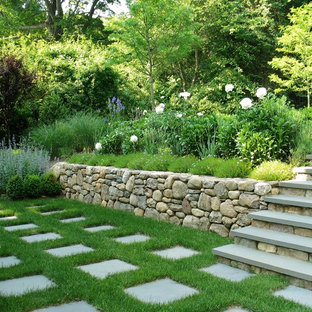 Photo of a large traditional partial sun backyard stone retaining wall landscape in New York.