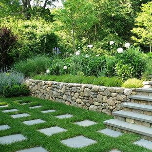 На фото: большой участок и сад на заднем дворе в классическом стиле с полуденной тенью, покрытием из каменной брусчатки и подпорной стенкой с