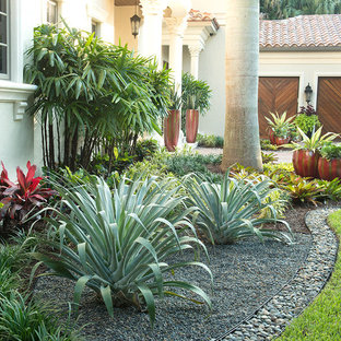 Design ideas for a large tropical partial sun front yard brick landscaping in Miami.
