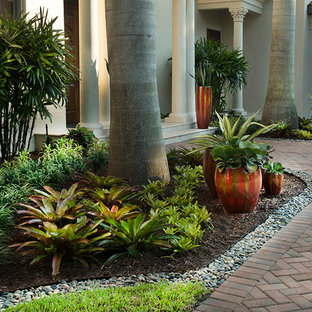 This is an example of a large tropical partial sun front yard brick landscaping in Miami.