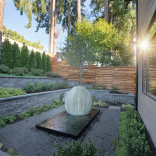 This is an example of a mid-sized modern rock and full sun backyard stone formal garden in Seattle.