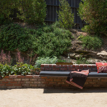 Bench seating in foreground with native plants on hillside in background