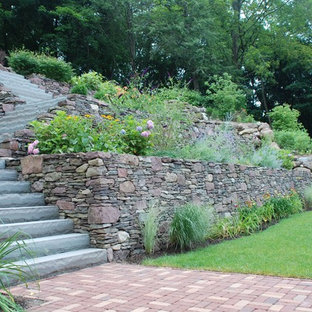 Inspiration for a medium sized classic sloped formal garden in New York with a garden path and natural stone paving.