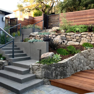 Design ideas for a mid-sized contemporary partial sun and drought-tolerant front yard wood fence retaining wall landscape in San Francisco with decking for summer.