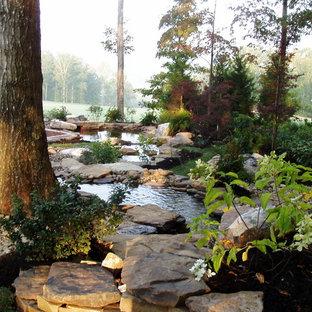 Modelo de jardín francés, clásico, grande, en patio trasero, con exposición reducida al sol y adoquines de piedra natural