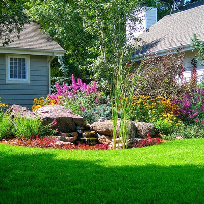 This is an example of a mid-sized traditional partial sun front yard mulch water fountain landscape in Other.