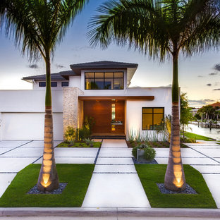 Photo of a mid-sized modern full sun front yard concrete paver driveway in Tampa for winter.
