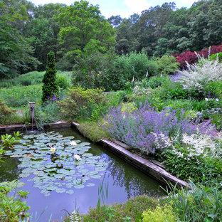На фото: большие геометрические участки и сады на заднем дворе в классическом стиле с полуденной тенью, мульчированием и прудом