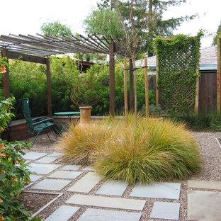 Réalisation d'un jardin arrière méditerranéen de taille moyenne avec une exposition partiellement ombragée et du gravier.