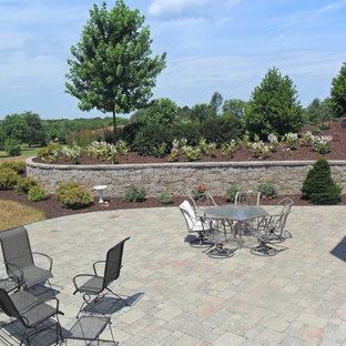 Cette image montre un jardin arrière traditionnel de taille moyenne avec un mur de soutènement, une exposition ensoleillée et des pavés en pierre naturelle.