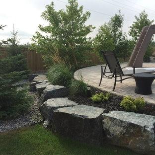 他の地域の大きい、夏のコンテンポラリースタイルのおしゃれな裏庭 (日向、マルチング舗装、擁壁) の写真