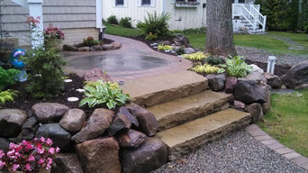 boulder walls and shade plantings surrounding sandstone steps with bluestone/bri