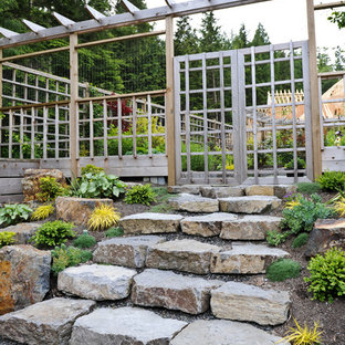 Photo of a transitional hillside stone landscaping in Vancouver.