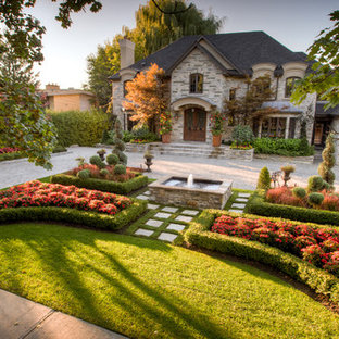 Photo of a large traditional full sun front yard brick landscaping in Toronto for summer.
