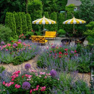 Aménagement d'un jardin à la française latéral classique de taille moyenne avec des pavés en pierre naturelle, une exposition ensoleillée et un massif de fleurs.