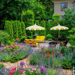 Foto på en mellanstor vintage formell trädgård i full sol längs med huset, med naturstensplattor