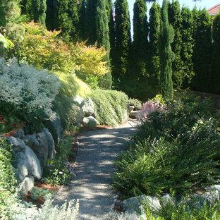 Réalisation d'un jardin tradition l'automne avec une pente, une colline ou un talus et du gravier.
