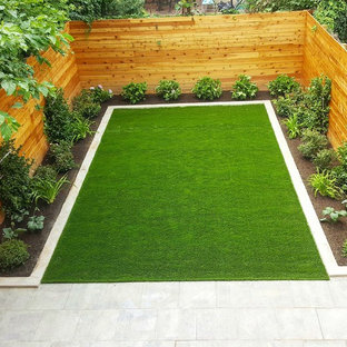 This is an example of a mid-sized modern full sun backyard concrete paver landscaping in New York.