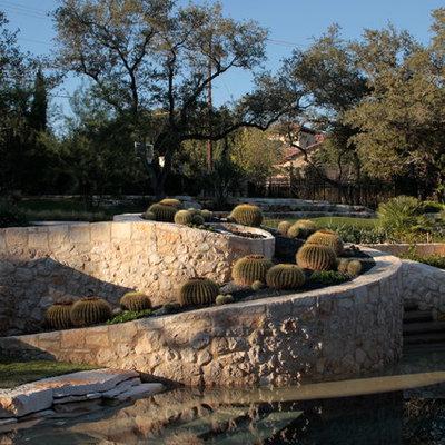 Photo of a mediterranean backyard retaining wall landscape in Austin.
