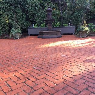 Idee per un grande giardino classico in ombra dietro casa con fontane e pavimentazioni in mattoni