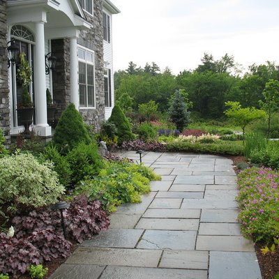 This is an example of a traditional full sun front yard stone garden path in Burlington.