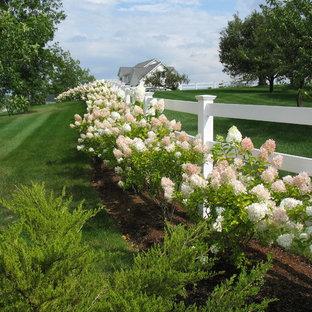 Design ideas for a huge farmhouse full sun backyard landscaping in Burlington.