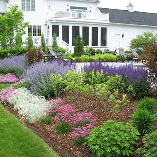 This is an example of a traditional full sun backyard stone landscaping in Burlington.