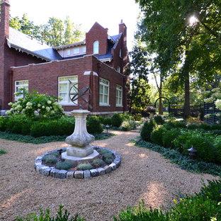 Immagine di un grande giardino formale classico esposto a mezz'ombra dietro casa con ghiaia e un ingresso o sentiero