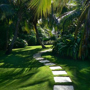 Immagine di un giardino tropicale in ombra con un ingresso o sentiero e pavimentazioni in pietra naturale