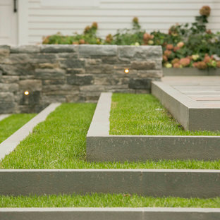 This is an example of a mid-sized contemporary backyard stone landscaping in Boston.
