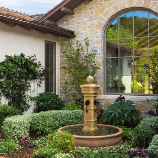 This is an example of a mid-sized mediterranean full sun backyard brick landscaping for spring.