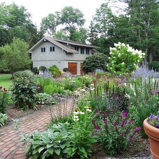 Bild på en liten vintage trädgård i full sol framför huset på sommaren, med en trädgårdsgång och marksten i tegel