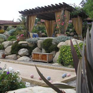 Inspiration för stora medelhavsstil bakgårdar, med en stödmur och grus
