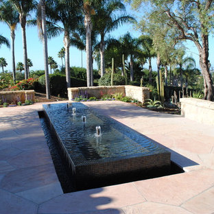 This is an example of a large transitional backyard garden in Santa Barbara with a water feature and natural stone pavers.
