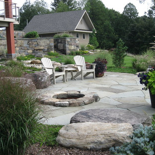This is an example of a huge rustic full sun backyard stone landscaping in Burlington with a fire pit for summer.