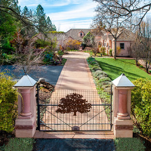 This is an example of a traditional partial sun front yard driveway in Sacramento.