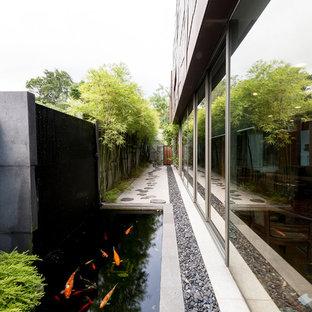 Halbschattiger Moderner Garten mit Wasserspiel und Natursteinplatten in Singapur