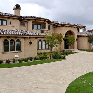 Photo of a large mediterranean front yard concrete paver driveway in Los Angeles.
