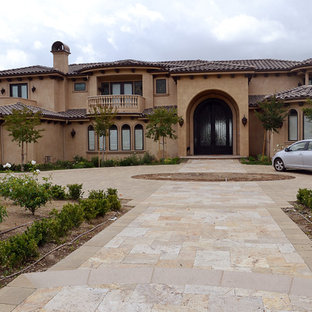 This is an example of a large mediterranean front yard concrete paver driveway in Los Angeles.