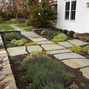 Пример оригинального дизайна: большой геометрический, солнечный участок и сад на заднем дворе в стиле кантри с подпорной стенкой, освещенностью и покрытием из каменной брусчатки
