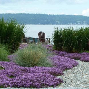 Kleiner Maritimer Garten hinter dem Haus, im Sommer mit direkter Sonneneinstrahlung, Blumenbeet und Flusssteinen in Seattle