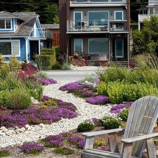 Cette photo montre un jardin à la française avant bord de mer avec un foyer extérieur et des pavés en pierre naturelle.